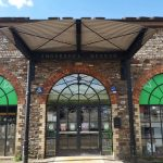 Front of industrial looking build entrance under shelter centre flanked by one brick arch on either side