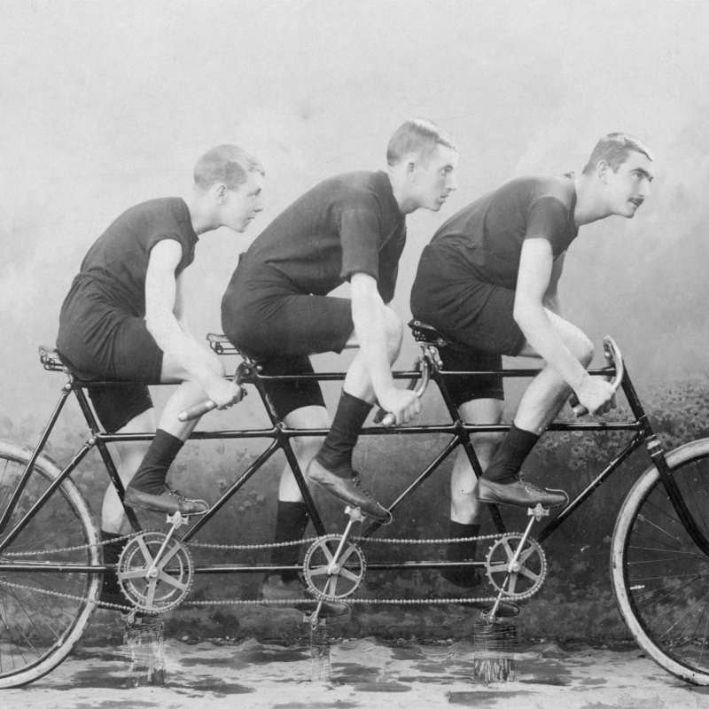 image if triple tandem being rode by 3 men, image black and white
